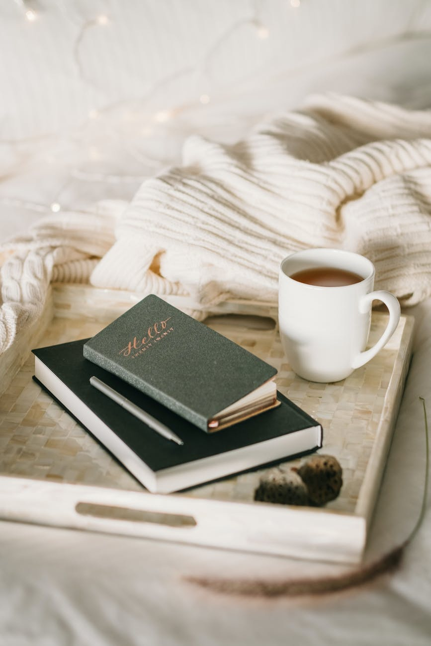 photo of cup beside books of journals to journal and call in your ideal relationship