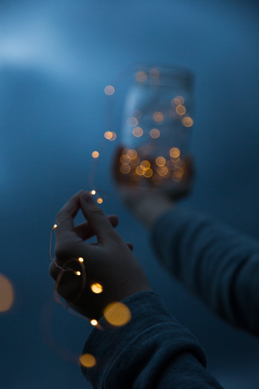 woman holding a yellow string light manifesting and calling in healthy love