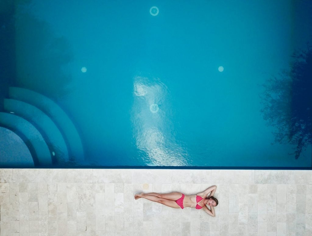 A woman laying beside a big pool closing her eyes and using financial affirmations