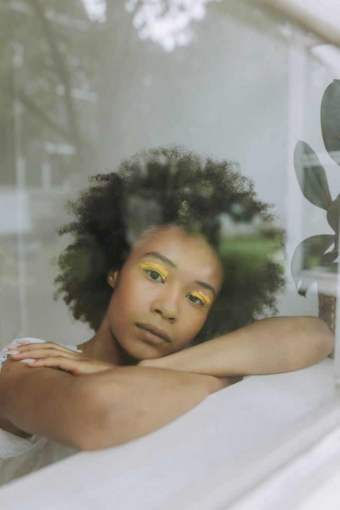 A woman looking out the window feeling vulnerable with herself