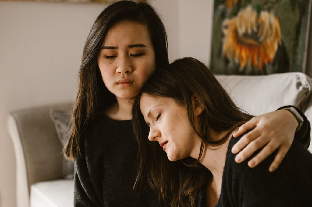 Two women hugging and helping each other due to being in toxic relationships