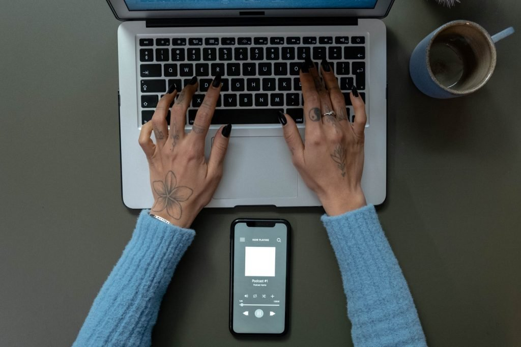 Woman typing onto a computer and listening to a podcast from her phone